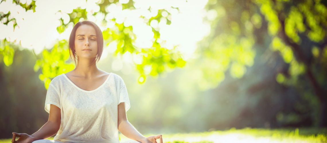 Young girl meditating in the park